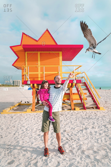 Father carrying daughter feeding seagull while standing at Miami beach- Florida- USA