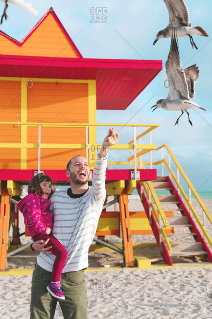 Happy father carrying daughter feeding seagulls while standing at Miami beach- Florida- USA