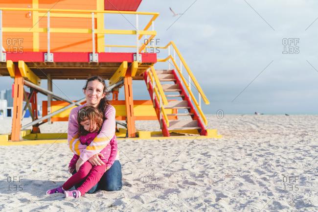 Loving mother embracing daughter at Miami beach against lifeguard hut- Florida- USA