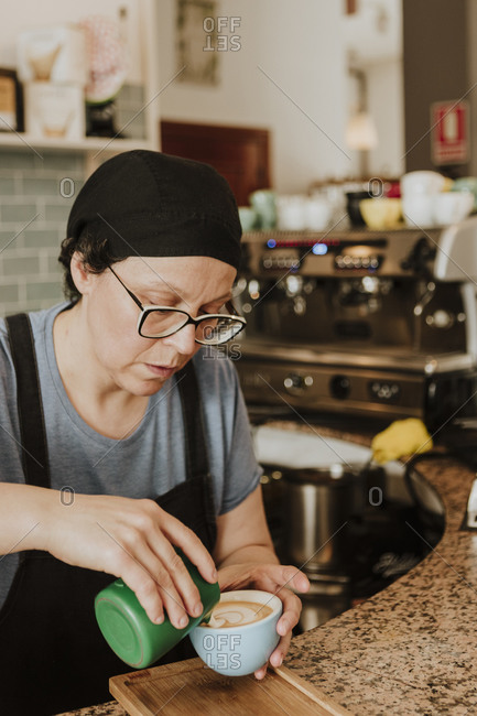 Portrait of waitress preparing Cappuccino in a coffee shop