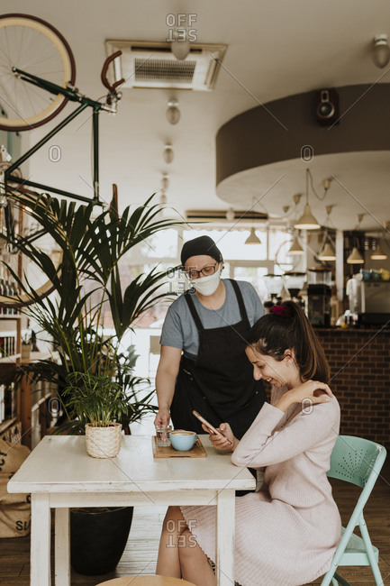 Waitress with protective mask serving Cappuccino in a coffee shop