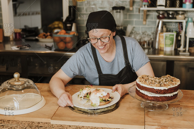 Portrait of smiling waitress serving food in a coffee shop