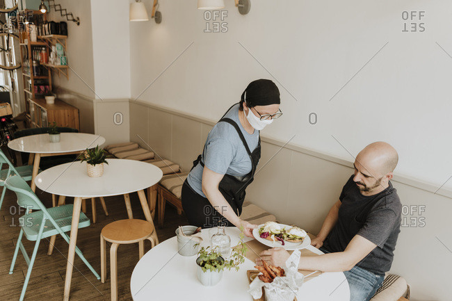 Waitress with protective mask serving food in a coffee shop