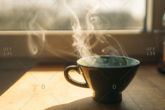 Steam rising from freshly prepared coffee in cup on table at home