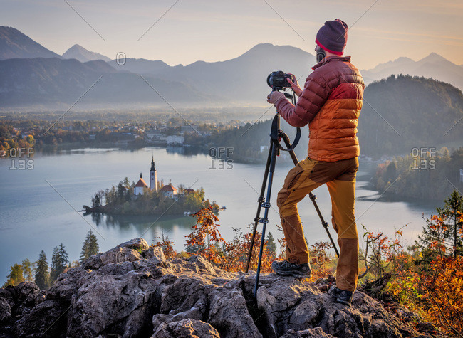 Slovenia- Upper Carniola- Bled- Man photographing Bled Island and Pilgrimage Church of Assumption of Maria at foggy dawn
