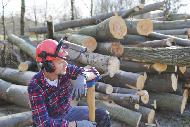Thoughtful lumberjack holding axe while sitting by logs in forest