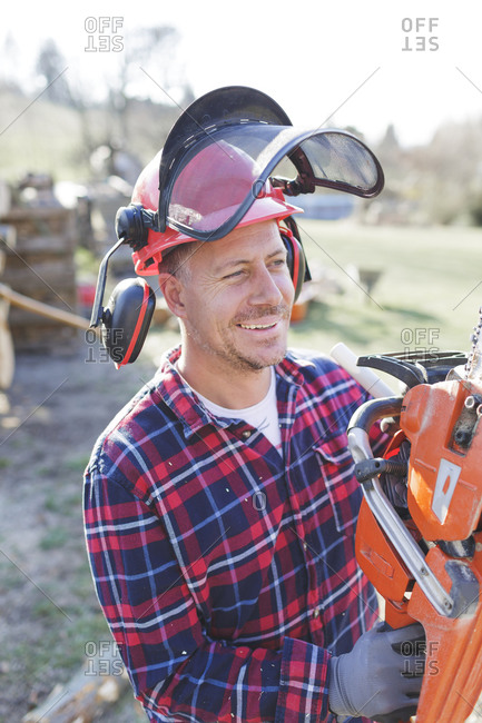 Thoughtful lumberjack holding chainsaw during sunny day
