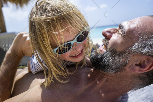 Close-up of cheerful girl wearing sunglasses playing with shirtless father at beach