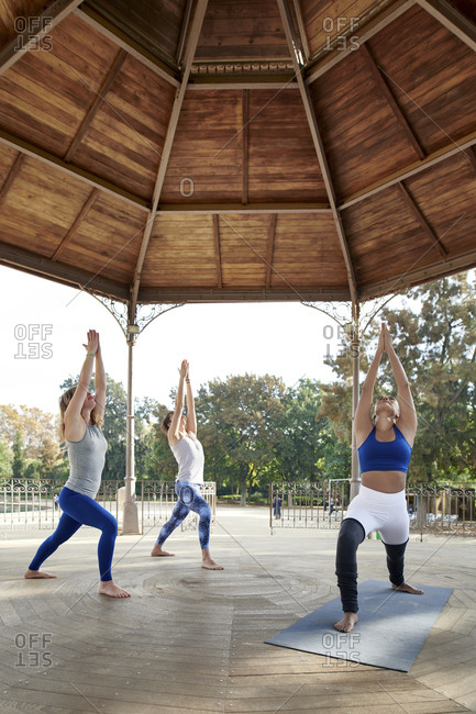 Female instructor practicing yoga in warrior position with man and woman in gazebo at Ciutadella Park