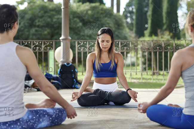 Yoga instructor practicing lotus position with man and woman in gazebo at Ciutadella Park