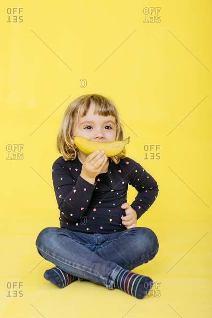 Full length of preschool girl holding banana while sitting with cross-legged and looking away against colored background