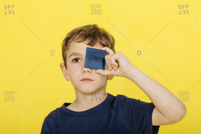 Close-up of cute boy holding blue acrylic glass against yellow background