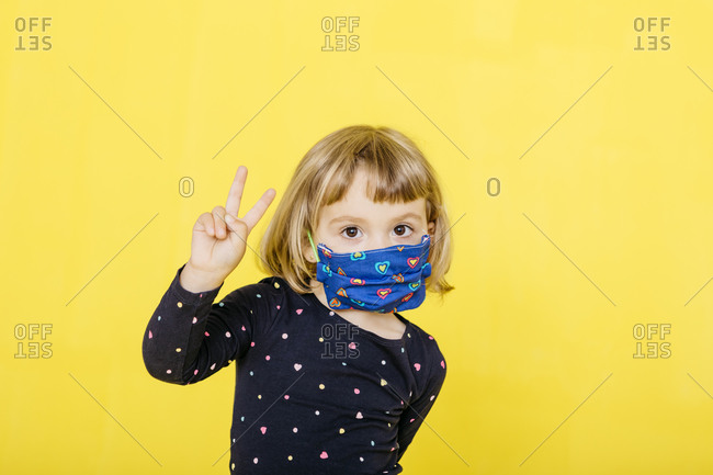 Portrait of cute blond girl wearing face mask and gesturing peace sign against yellow background