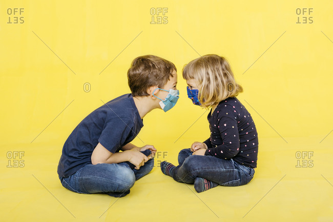 Side view of siblings sitting face to face against yellow background