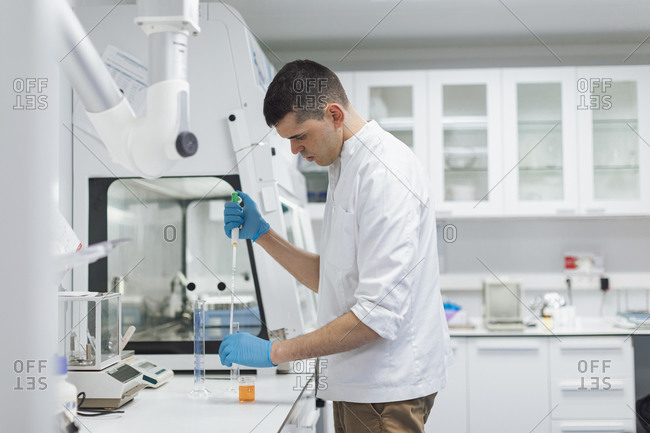 Young male scientist taking chemical with pipette while doing research in lab