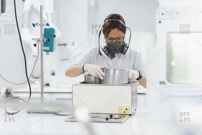 Confident female technician doing research while using medical equipment at laboratory