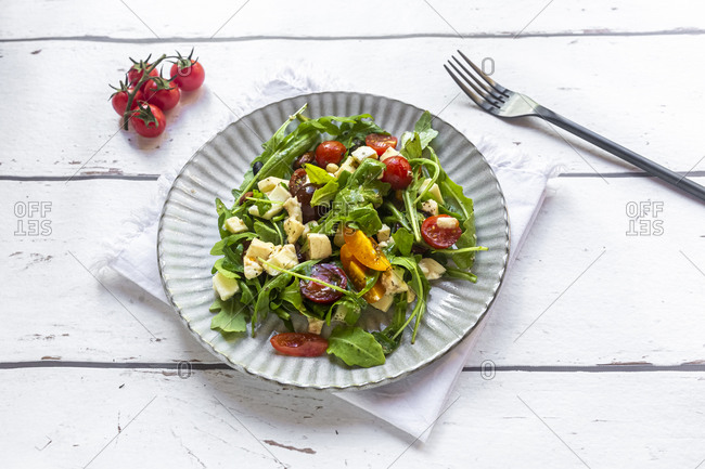 Plate of low carb vegetarian salad with arugula- tomatoes- nuts and Mozzarella cheese