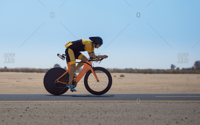 Determined cyclist riding bicycle on road at desert in Dubai- United Arab Emirates