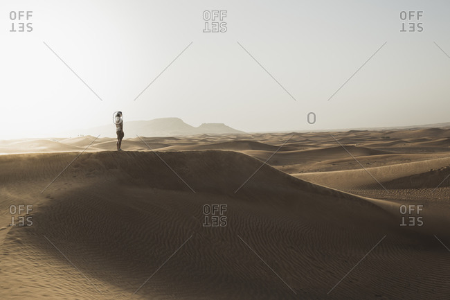 Mid distance of male tourist standing on sand dunes in desert at Dubai- United Arab Emirates