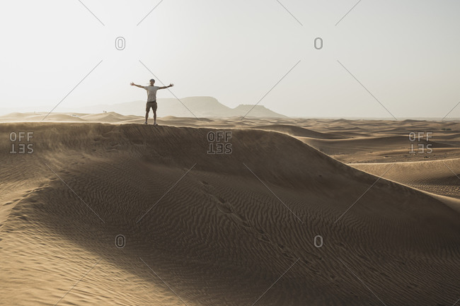 Mid distance of male tourist standing with arms outstretched on sand dunes in desert at Dubai- United Arab Emirates