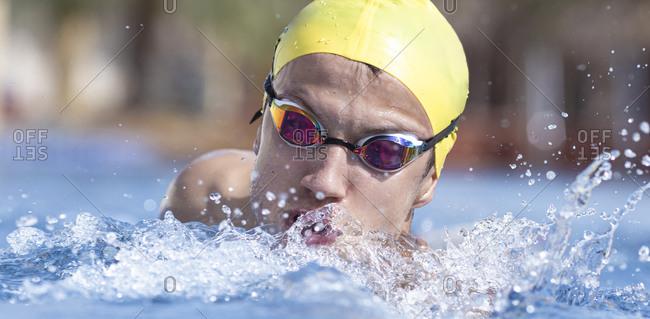 Determined male swimmer swimming in pool at tourist resort- Dubai- United Arab Emirates