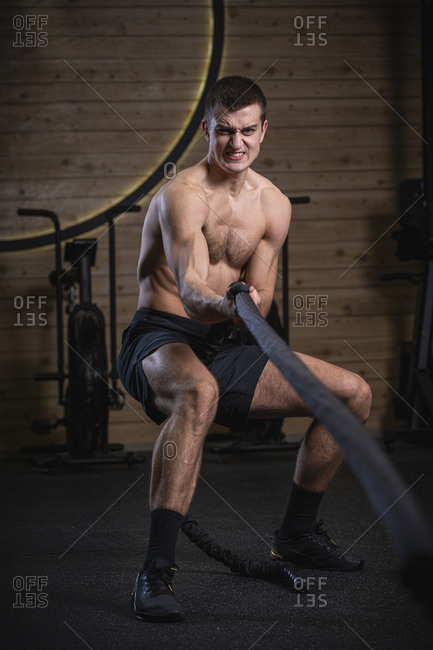 Strong and fit athlete pulling rope