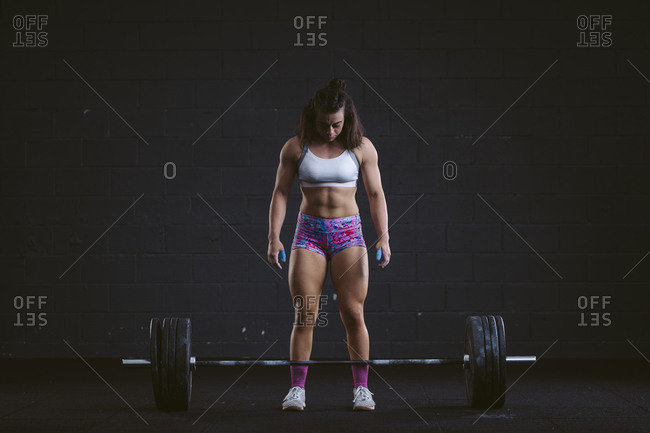 Young woman practicing barbell squat at gym