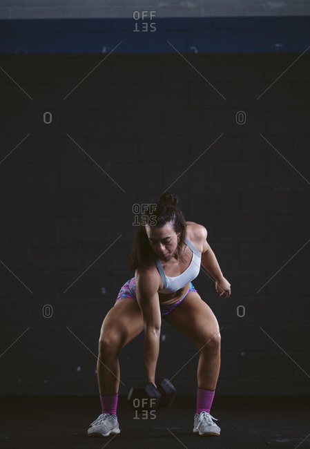 Athletic woman exercising with dumbbell at gym
