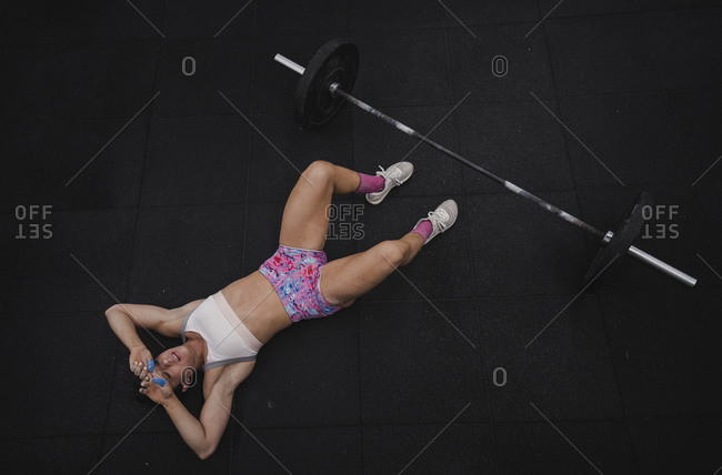 Young woman lying on floor after practicing barbell squat at gym