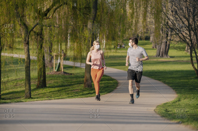 Couple wearing face masks while running on footpath at park