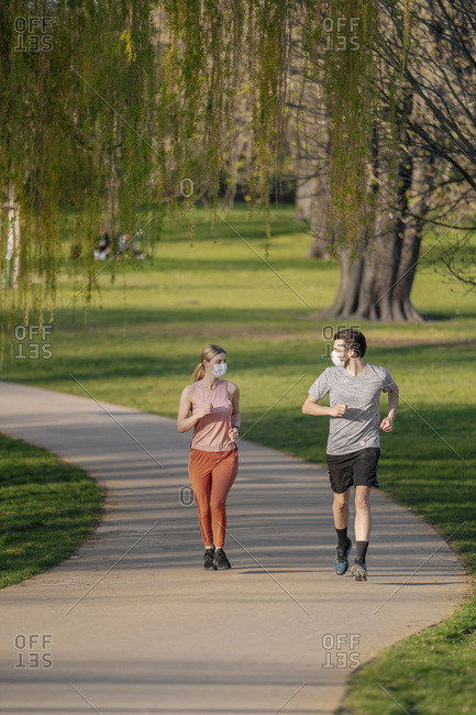 Couple wearing face masks while jogging on footpath at park