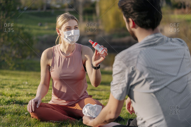 Woman wearing face mask showing hand sanitizer to man while sitting at park