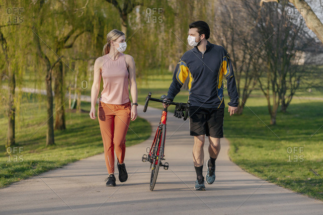 Young couple walking with bicycle on footpath at park during coronavirus pandemic