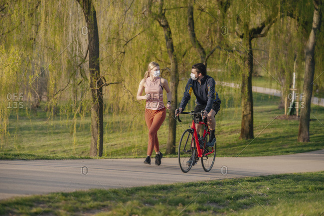 Man cycling by woman jogging on footpath at public park during COVID-19