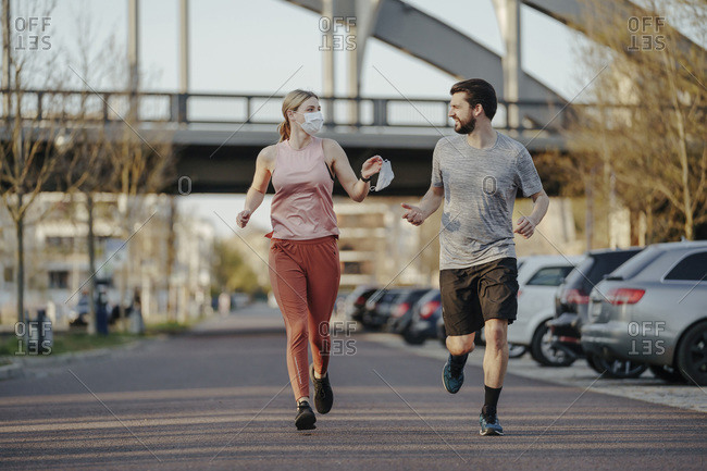 Young woman jogging while giving man face mask during COVID-19 pandemic