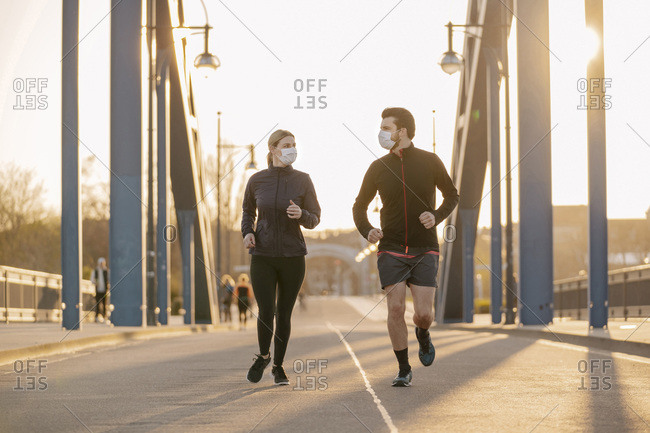 Young couple wearing face masks running on bridge in city during sunset