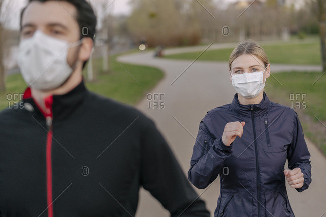 Young man and woman wearing face mask while jogging on footpath at park during COVID-19