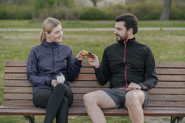 Smiling woman giving face mask to man while sitting on bench at park during quarantine