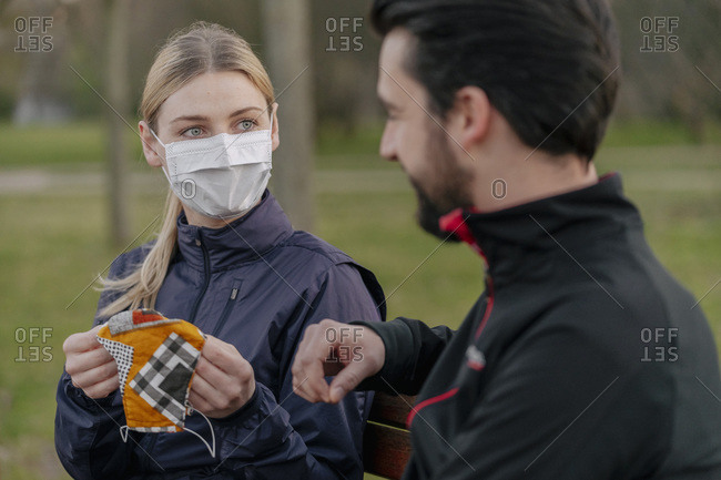 Young woman giving face mask to man while sitting at park during quarantine