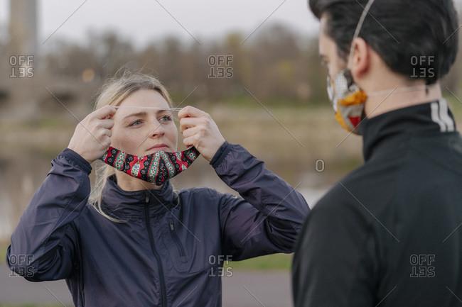 Woman looking at man while wearing face mask at park