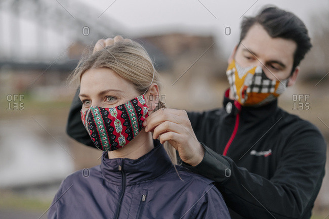 Young man adjusting face mask for woman while standing at park during COVID-19