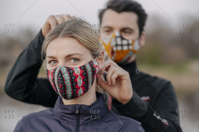 Portrait of young woman while man adjusting face mask for her at park