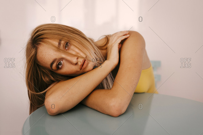 Beautiful young woman leaning on table at home