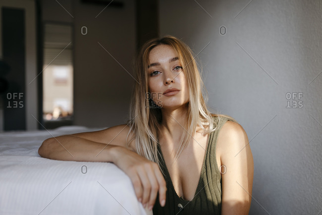 Seductive young woman sitting by bed in bedroom at home