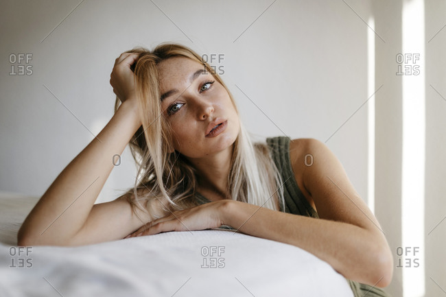 Seductive young woman with hand in hair leaning bed at home