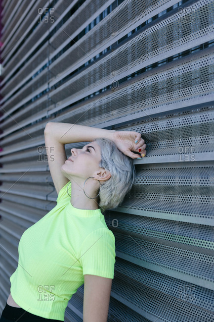 Blond woman leaning on metal background- daydreaming