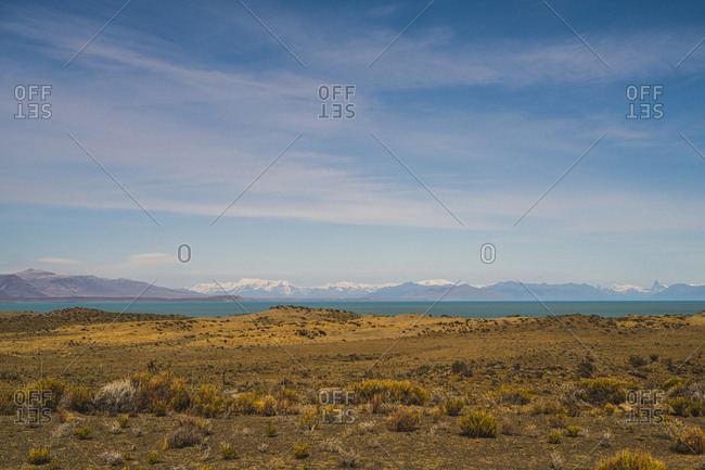 Argentina- Bushy plateau with lake and mountains in distant background
