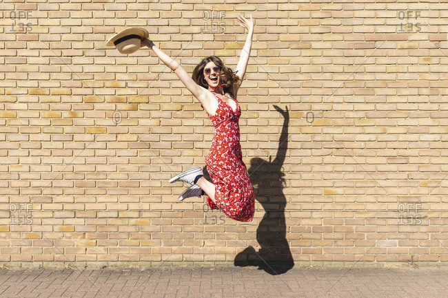 Happy young woman jumping and holding a straw hat