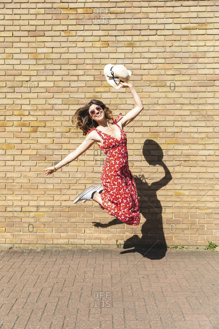 Happy young woman with straw hat jumping in front of wall