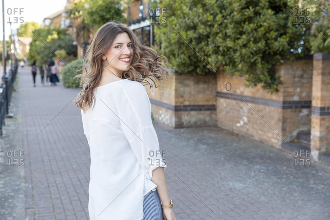 Young smiling woman looking back during stroll